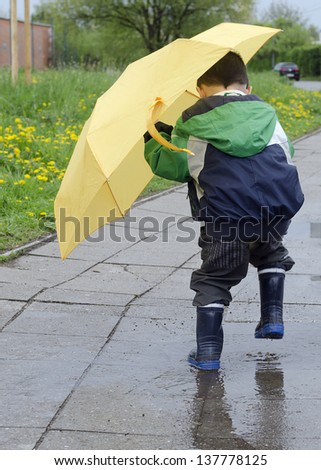 Child with a yellow umbrella jumping into a puddle after the rain. - stock photo