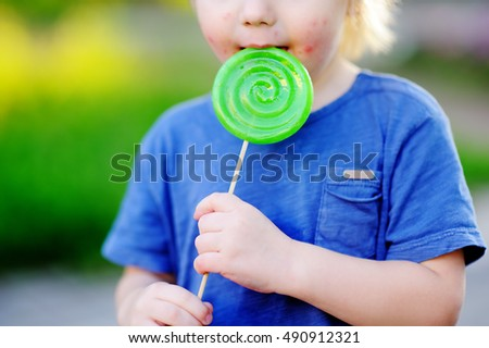 Child with allergic reaction eating big green lollipop. Unhealthy sweet food for young kids. Allergic rash dermatitis on toddler skin face.