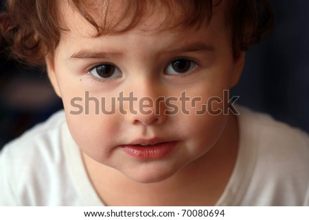 child with an interesting look, and brown eyes looking into the camera