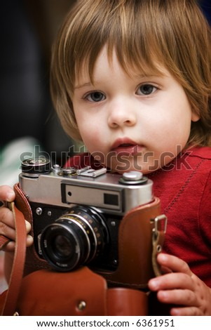 Child with an old photo camera - stock photo
