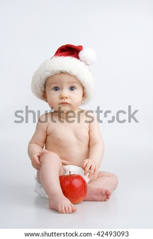 Child with apple and Christmas bonnet on white background. - stock photo