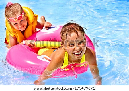 Child with armbands in swimming pool. - stock photo