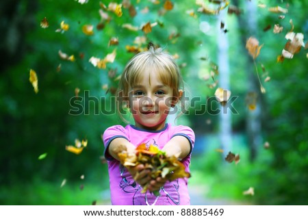 child with autumn leaves - stock photo