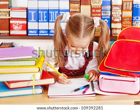 Child with backpack writing in classroom.