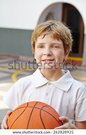Child with basketball in physical education class in school - stock photo