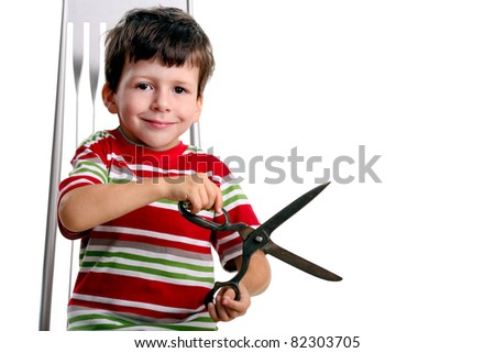 Child with big scissors sit on chair, isolated on white - stock photo