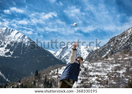 Child with blue jacket have fun with snowball fight winter outdoor,Greece,Platira lake - stock photo