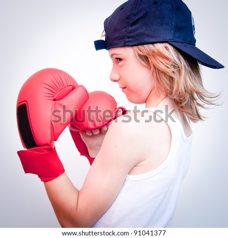 child with boxing gloves and hat - stock photo