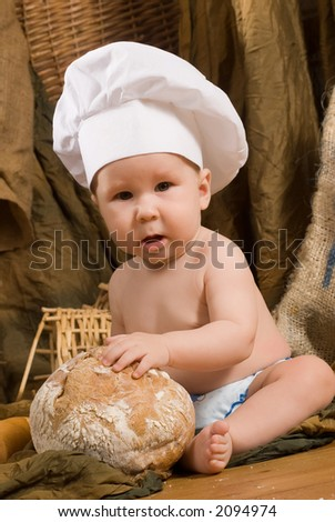 child with bread on bakery-like background wearing cook-hat - stock photo