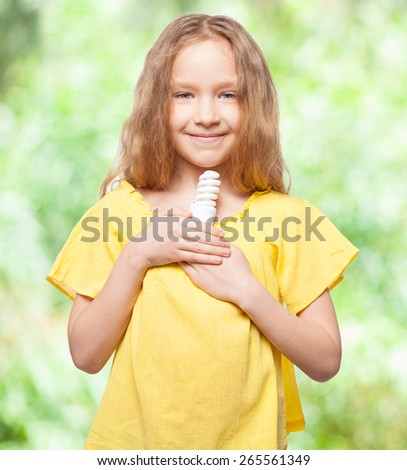 Child with bulb. Girl holding an energy saving lamp - stock photo