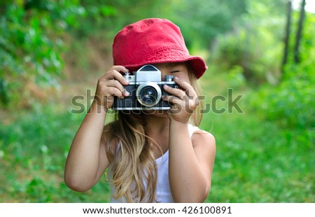 Child with camera. Little girl photographing. Beautiful little girl with photo camera. Child photographer holding a camera at the park. Young photographer in nature. - stock photo