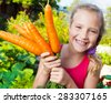 Child with carrot. Girl with vegetables in garden - stock photo