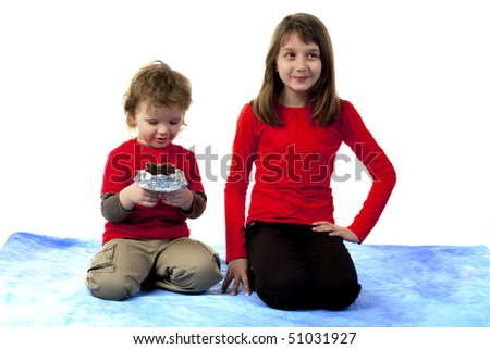 Child with chocolate and a girl looking away - stock photo