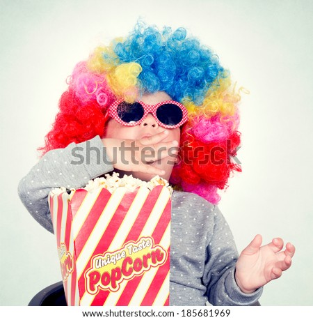 Child with clown wig and sunglasses eating pop corn - stock photo
