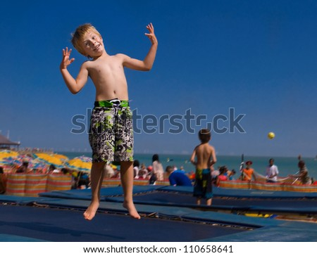 Child with crazy expression jumping on a trampoline. - stock photo