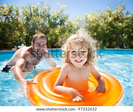 Child with dad playing in pool. Summer vacations - stock photo