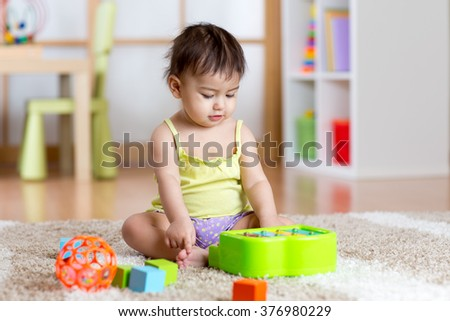 Child with develepmental toys. Early education for kids. Colorful wooden art toys. Little girl play music. Kid with piano.  - stock photo