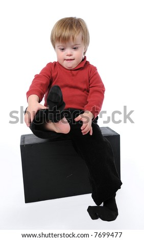 Child with down syndrome putting his socks on isolated on white