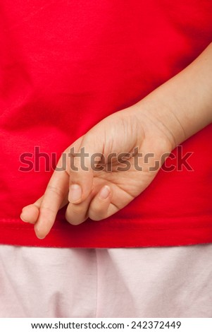 Child with fingers crossed behind her back to excuse telling a lie   - stock photo