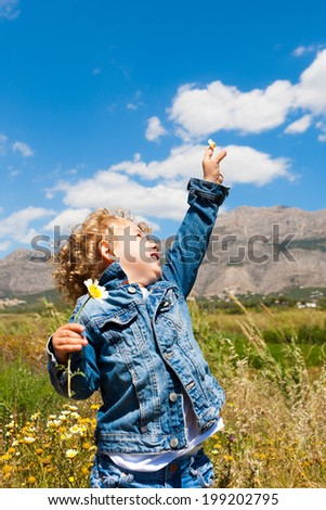 child with flower in the field - stock photo