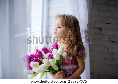child with flowers in the window - stock photo