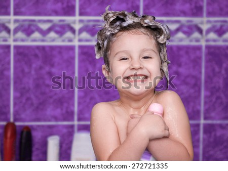 Child with foam in hair smiling - stock photo