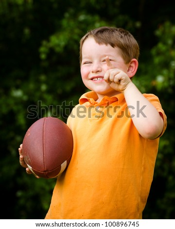 Child with football celebrating by showing that he's Number 1 - stock photo