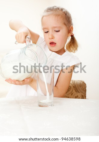 Child with glass pitcher milk. Little girl drinking milk at home
