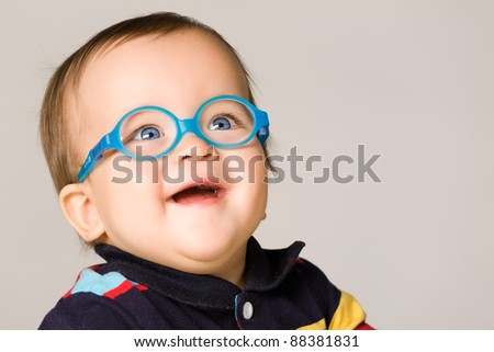 Child with glasses, close-up. On gray background. - stock photo