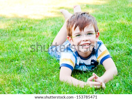 Child with glasses lying on grass  - stock photo