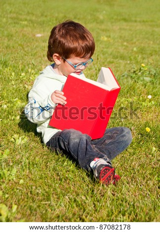 Child with glasses reading a red book sitting on grass - stock photo