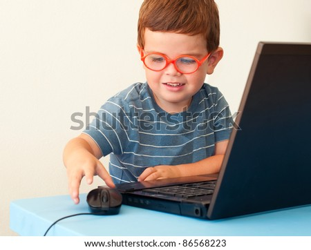 Child with glasses using computer and mouse