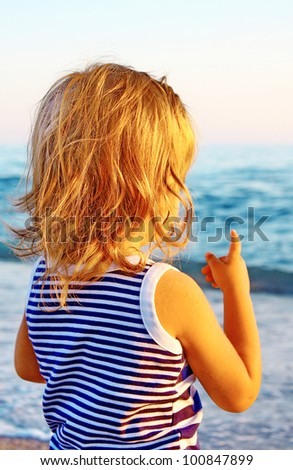 Child with golden hair on sunset beach - stock photo