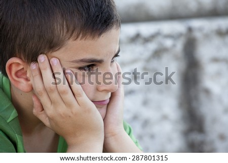 child with hands on chin - stock photo