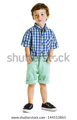 Child with hands on pockets isolated on white./ Portrait of a little boy in studio. - stock photo