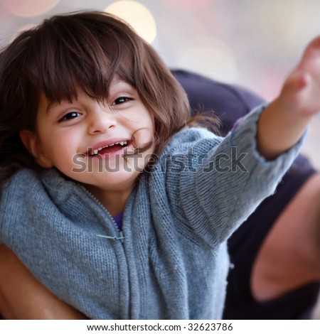 Child with happiness in eyes, feeling kindness of the world up to tips of fingers and its iridescent paints. - stock photo