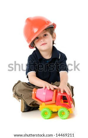 Child  with hard hat playing sitting on the floor - stock photo