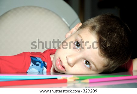 Child With Head on Table Looking Bored