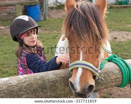 Child with helmet stroking pony on a farm - stock photo