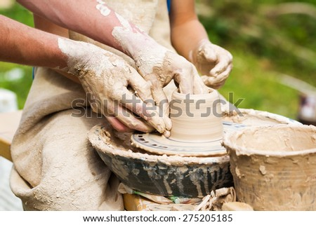Child with help of master hands working on pottery wheel and making clay pot - stock photo