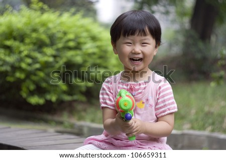 child with her water pistol - stock photo