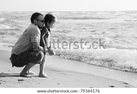child with his father at sea - stock photo