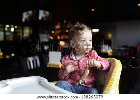 Child with kebab in a high chair at a restaurant - stock photo