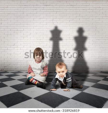 child with king and queen shadows on a checkered floor - stock photo