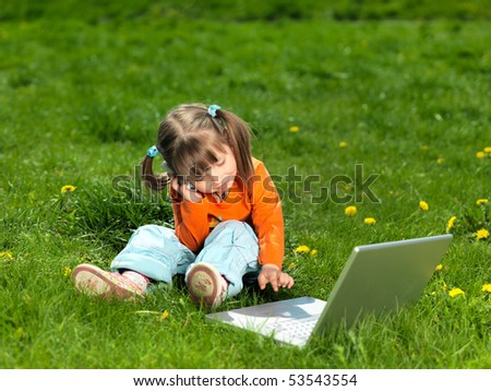 child with laptop in a grass field - stock photo