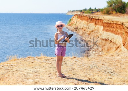 child with laptop on the rock - stock photo