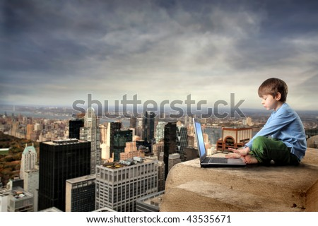 child with laptop on the top of NY city - stock photo