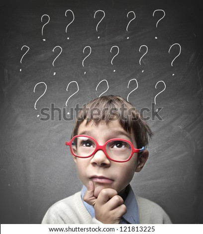 Child with many question marks - stock photo