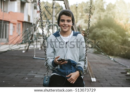 child with mobile phone on swing on city street
