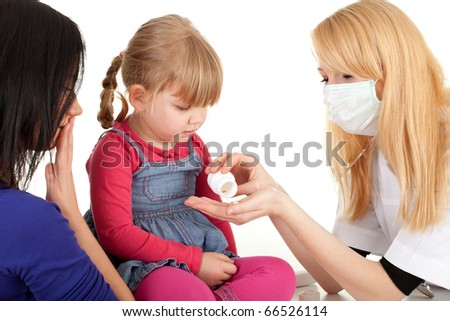 child with mother at doctor - female doctor showing drugs  and examining little girl - stock photo